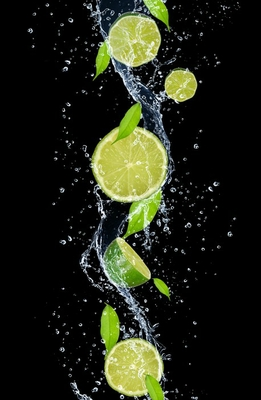 Limes in water splash, isolated on black background