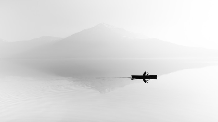 Fog over the lake. Silhouette of mountains in the background. The man floats in a boat with a paddle. Black and white Poster - Hobbies and Leisure