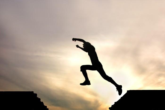 Tableau sur Toile Silhouette de saut garçon contre le coucher du soleil - Thèmes
