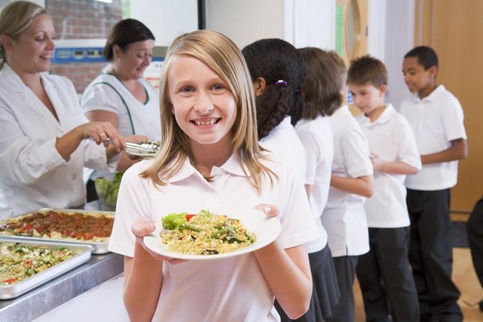 Uczennica trzyma talerz z obiadem w szkolnej stołówce