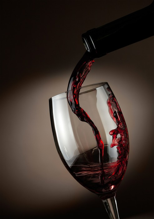 Red Wine Pouring In Glass Over Dark Background Wall Mural