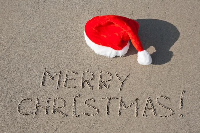 Vinylová Tapeta Merry Christmas napsaný na písečné pláži v červeném klobouku Santa - Mezinárodní svátky