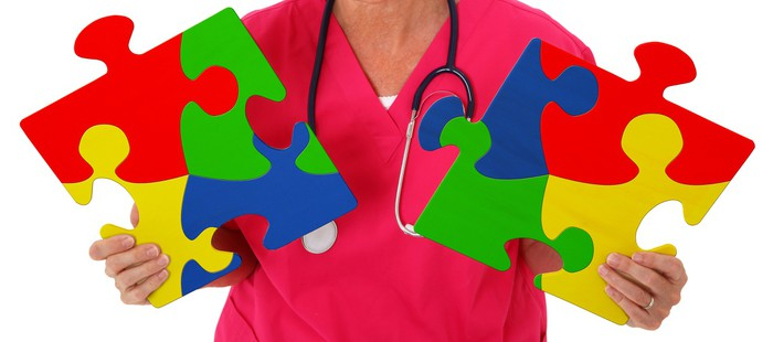 Nurse Holding Two Puzzle Pieces Representing Autism Awareness Vinyl Wallpaper - Health and Medicine