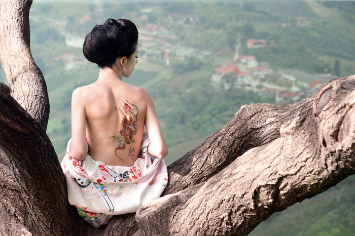 Woman with snake tattoo sitting on tree branch (Orig) Vinyl Wallpaper - Tattoos