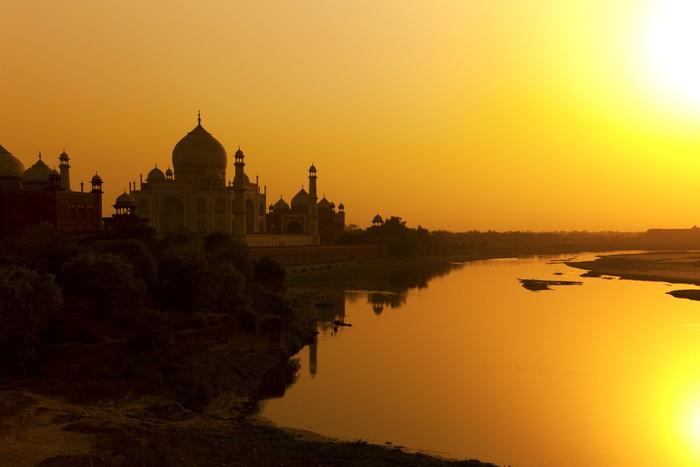 Taj Mahal z rzeki Jamuny o zachodzie słońca, w Indiach.