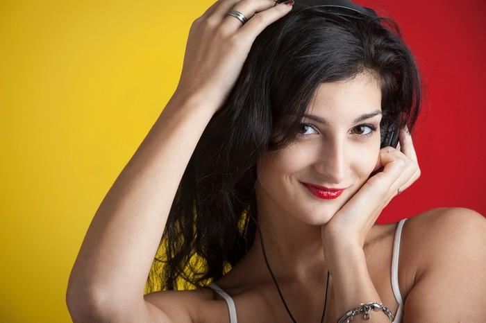 Vinylová fototapeta Dívka se sluchátky proti červené a žluté pozadí. - Vinylová fototapeta