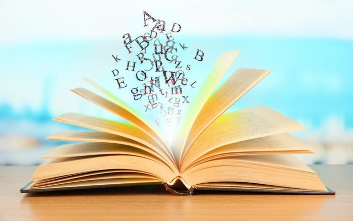 Carta da parati libro aperto con lettere su sfondo for Foto di un libro