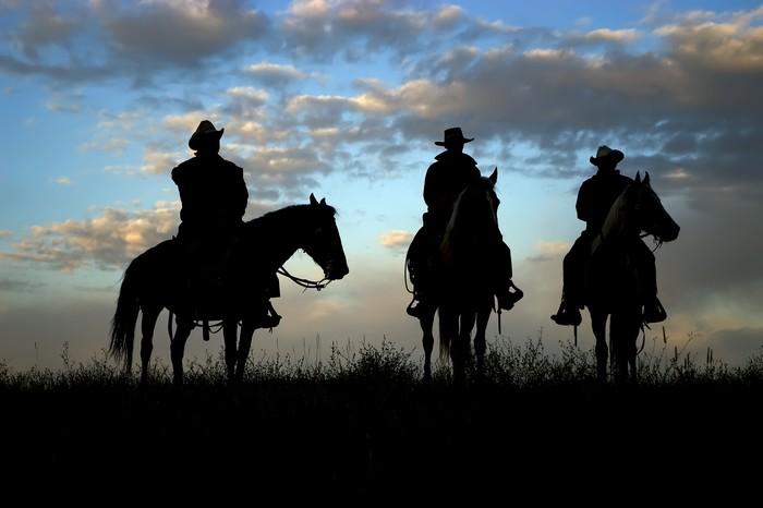 Vinylová fototapeta Tři kovbojové na koních siluetu proti obloze svítání - Vinylová fototapeta