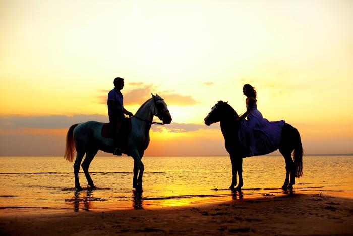 Vinylová Fototapeta Dva jezdci na koních při západu slunce na pláži. Milovníci jízdy hors - Vinylová Fototapeta
