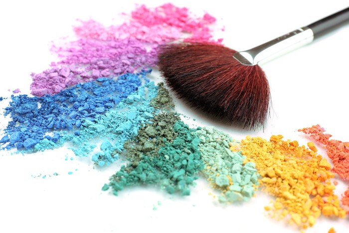 rainbow crushed eyeshadow and professional make up brush close wall
