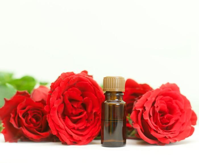 Nálepka Pixerstick Láhev aromaterapie oleje a zářivě rudých růží, kosmetický salón - Životní styl, péče o tělo a krása