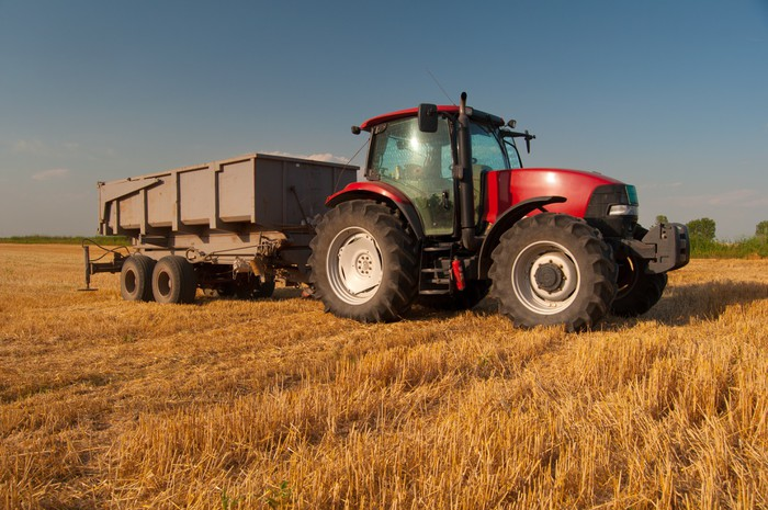 Vinylová Tapeta Moderní červená traktor na oblasti zemědělství na slunné letní den - Zemědělství