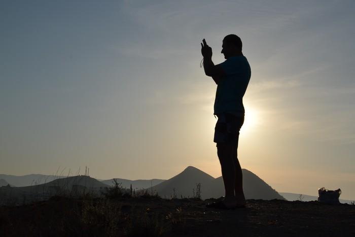 Vinylová Tapeta Турист на горе, тень силуэта на солнце - Prázdniny
