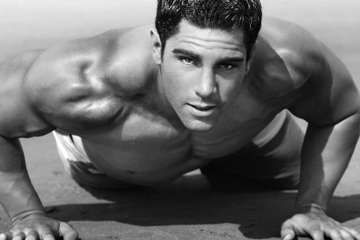 Leinwandbild Junger Mann mit nacktem Oberkörper tun Push-ups am Strand - Bereich